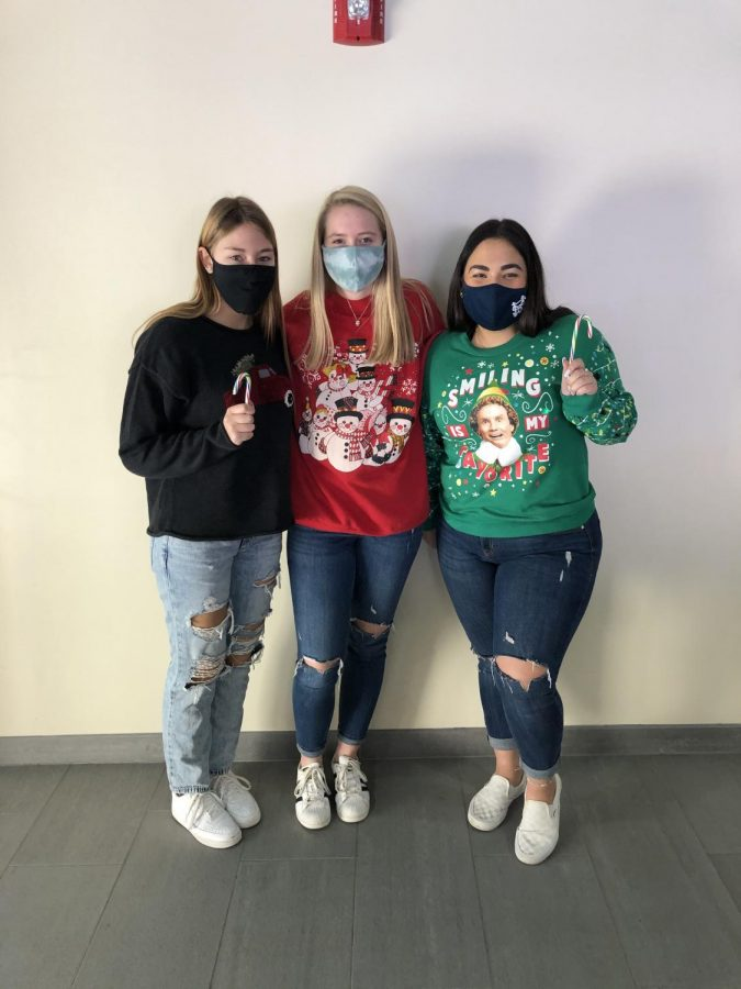 Regan Franzoni, Madelyn Dunham, and their other friend in their best ugly sweaters showing some holiday spirit