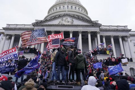 Trump Supporters climb and gather on the Capitol building Image via Los Angeles Times