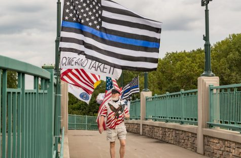 Man walking underneith a thin blue line flag and an american flag