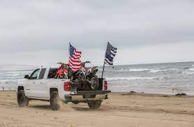 Truck driving across a beach with an american flag and a thin blue line flag on the back of it